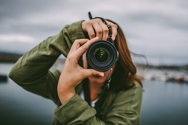A young woman using a DSLR camera